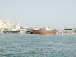 Across the Sharjah channel to a fat wooden dhow loaded high.